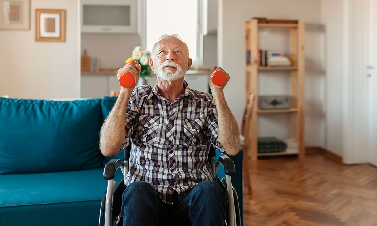 Man in wheelchair lifting weights at home