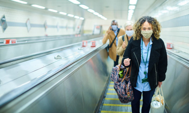 commuters on escalator wearing masks