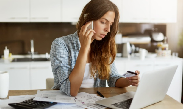 woman on the phone holding a credit card