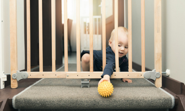 baby reaching through stair gate