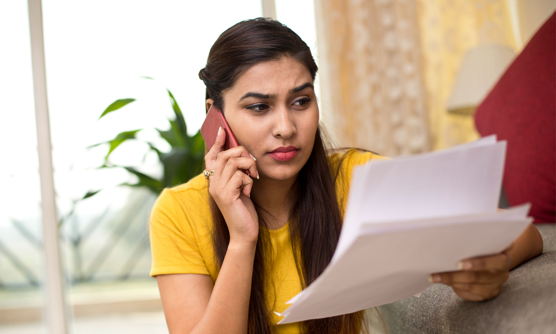 woman on the phone looking at a bill