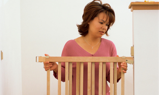 Woman installing a stair gate