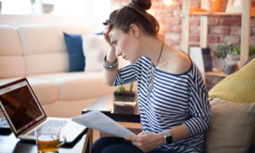 Woman looking at laptop with document in hand