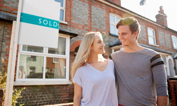 couple stood outside house with sold sign