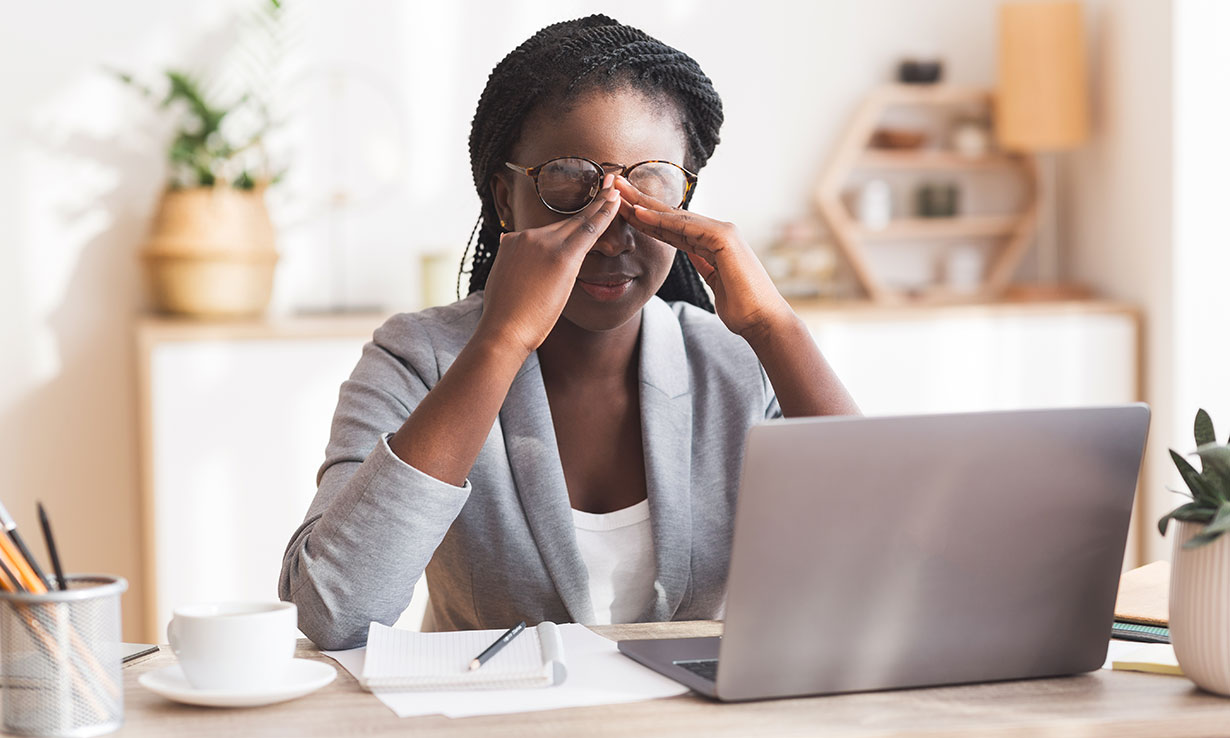 Woman sitting at a laptop frustrated