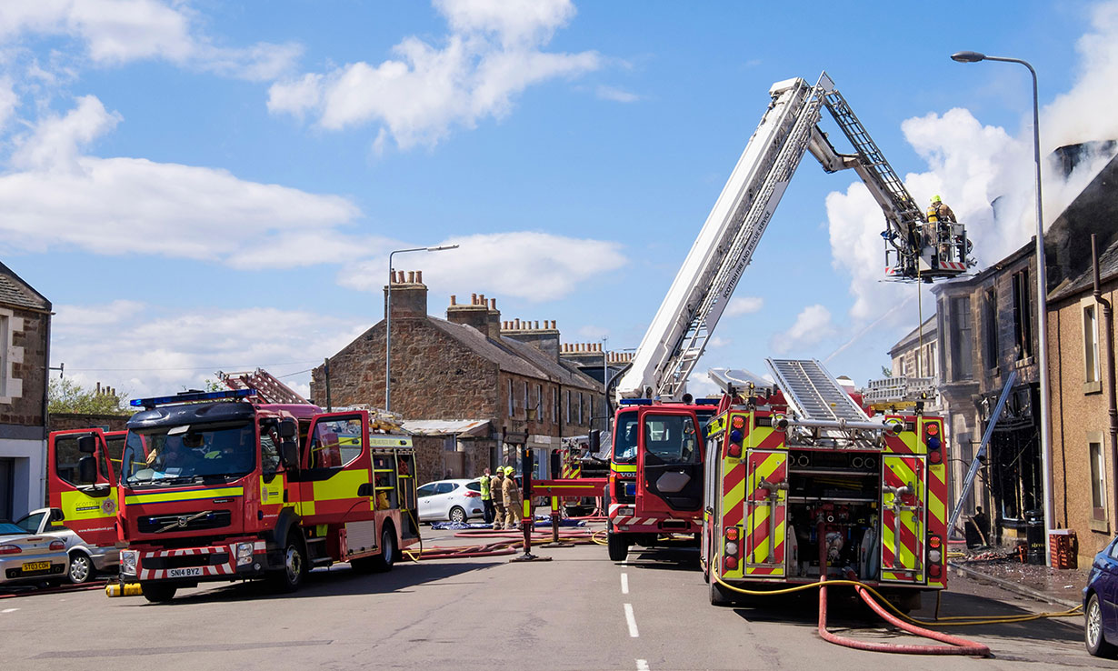 The fire brigade attending a house fire, with three fire engines in view.