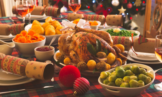 Christmas dinner spread including roast turkey, brussel sprouts, carrots, roast potatoes, peas, cranberry sauce and wine