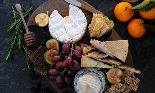 Christmas cheese board with grapes, crackers, figs, honey and oranges