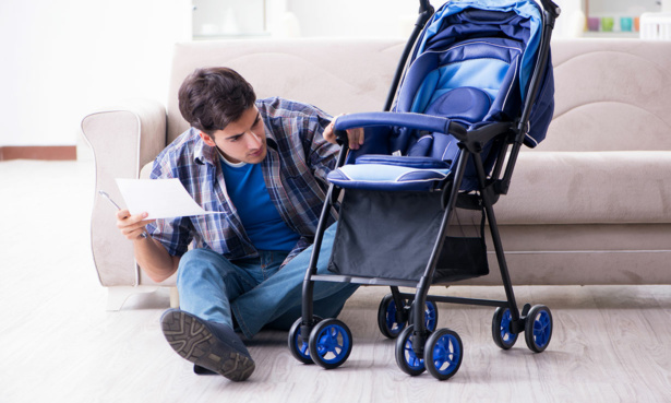 Person looking at pushchair instruction manual