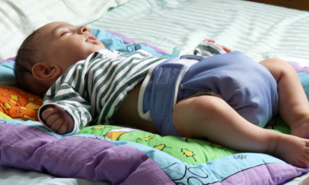 Sleeping baby wearing a reusable nappy