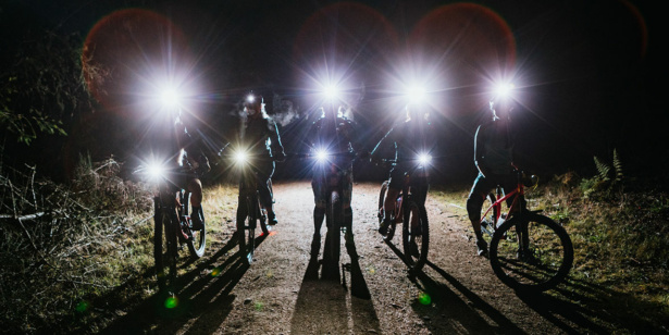 Cyclists in the dark with bike lights on.
