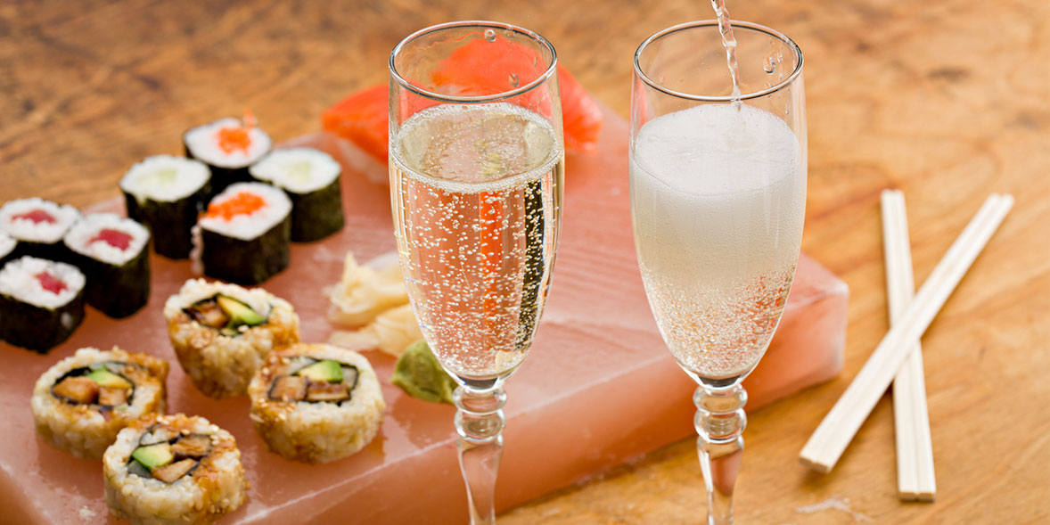 Sushi on a slab with two glasses of champagne
