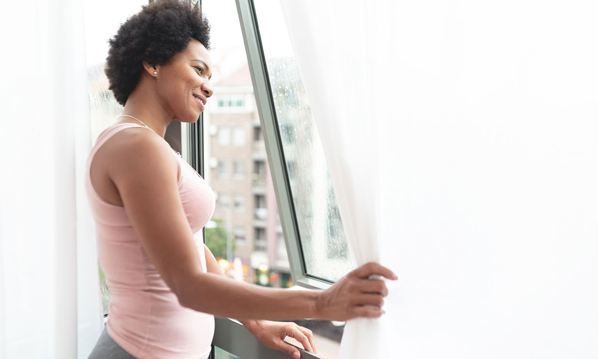 Woman next to an open window