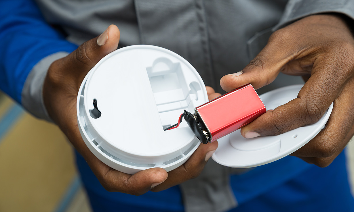 Man holding a smoke alarm with the back open and the battery on display.