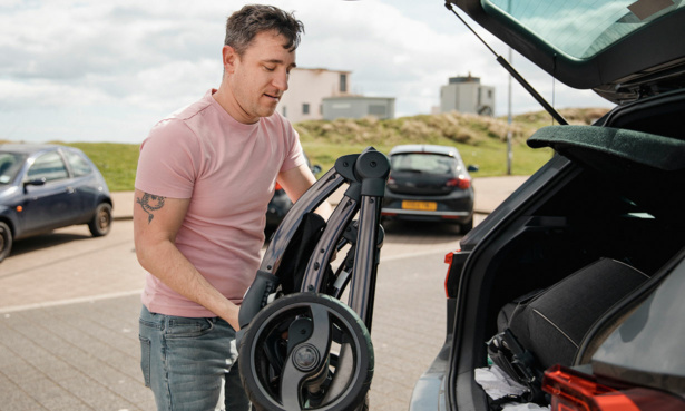 Person lifting folded pushchair into car boot