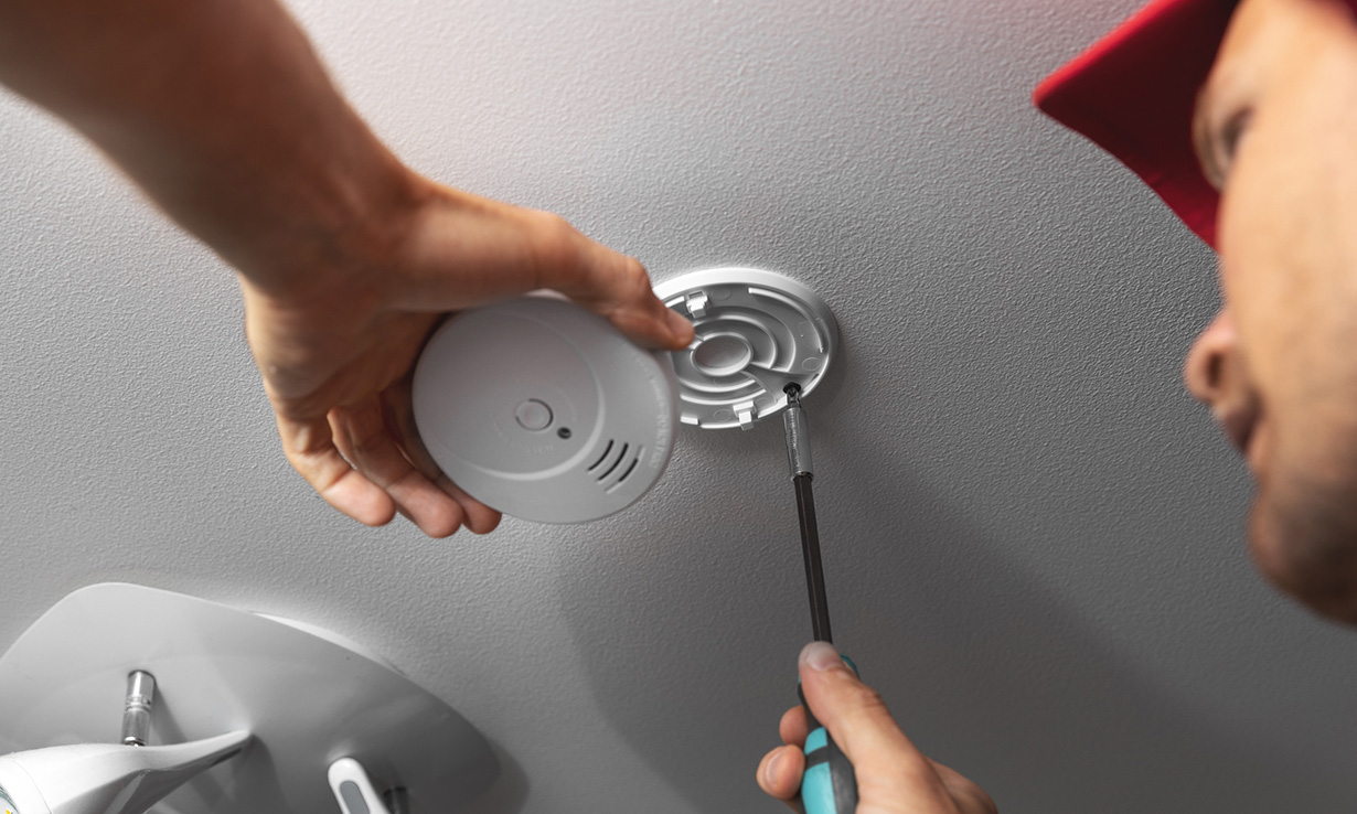 Man installing carbon monoxide alarm to ceiling in home