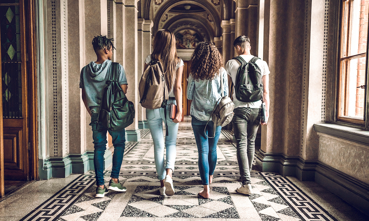 Four university students walking through a college hall.