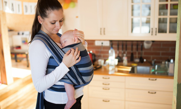 Woman holding a young baby in a sling