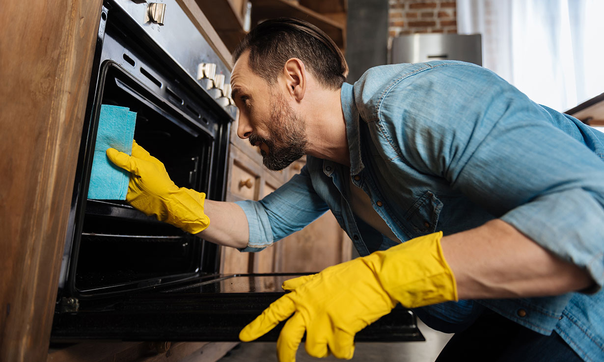 Man cleaning an oven