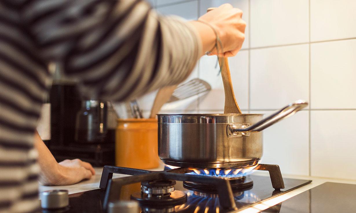person stirring a pan on a gas hob