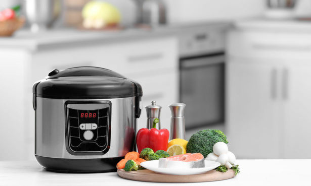 Electric pressure cooker with ingredients next to it
