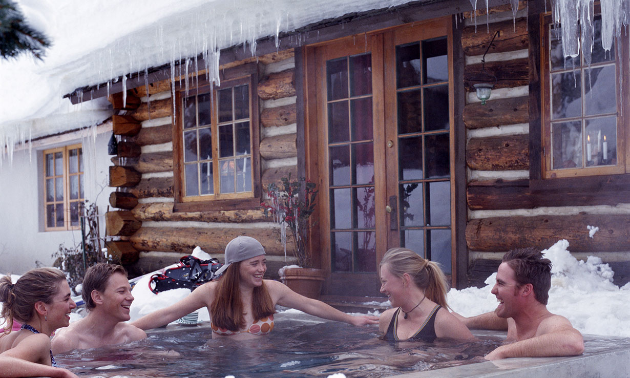 Hot tub outside a log cabin in a snowy garden