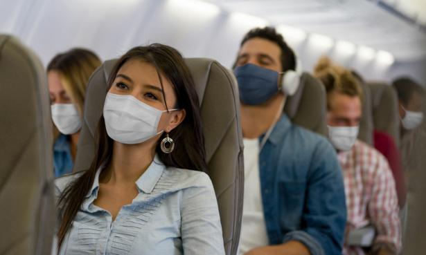 people on plane wearing masks