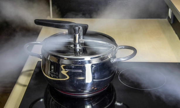 Pressure cooker on stove with steam escaping