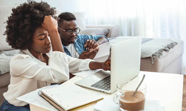 Woman and man distressed at laptop over refund