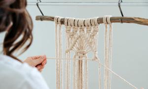 woman weaving a macramé hanger