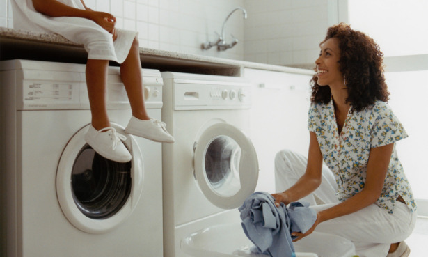 Woman using a dryer with a girl sitting on top of it - the woman is smiling at the girl.
