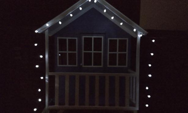 Solar lights ulluminating a childs playhouse.