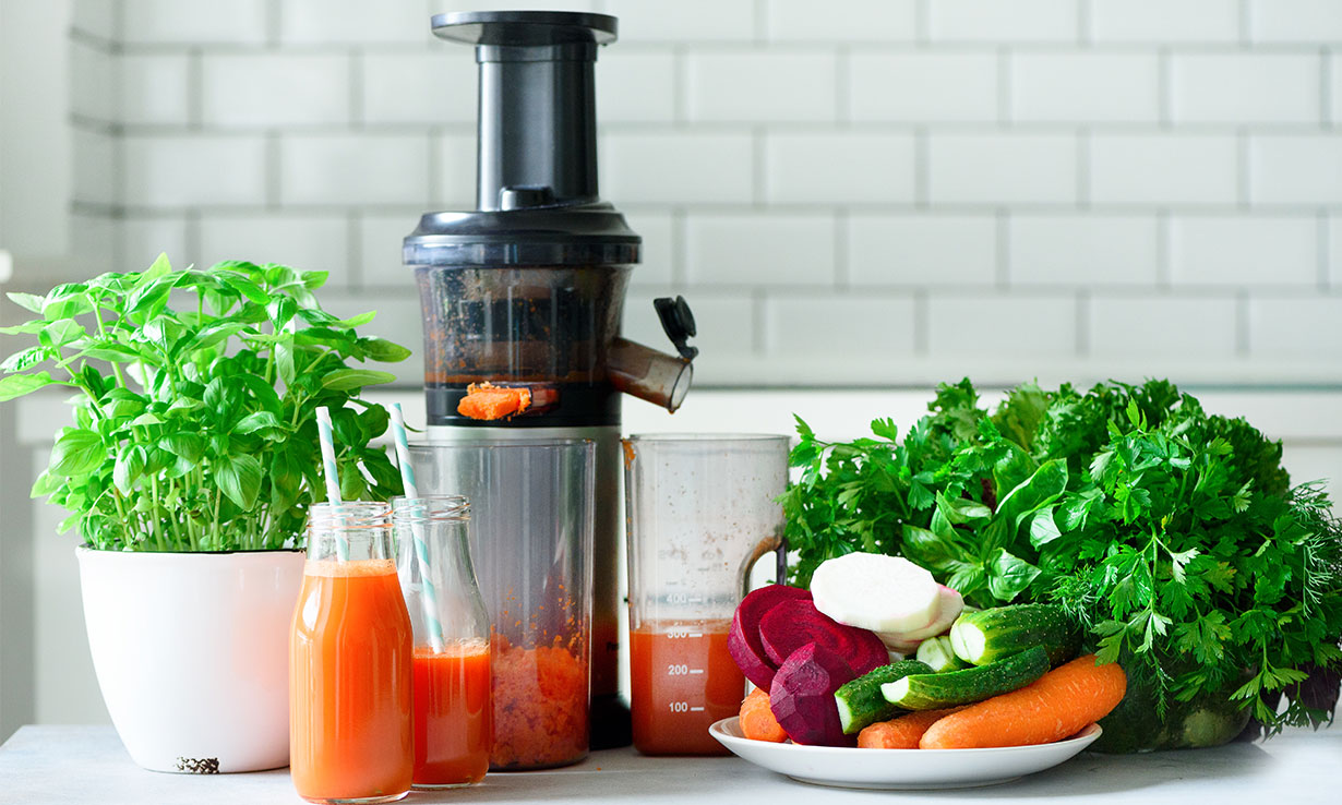 Juicer surrounded by vegetables