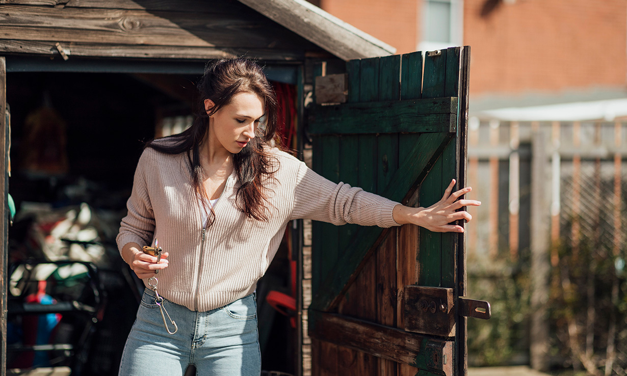 Woman putting things in a garden shed
