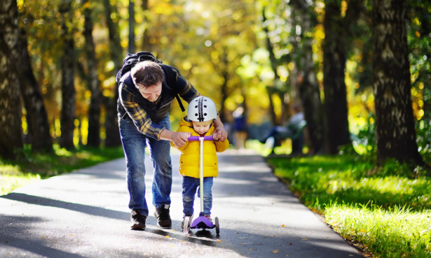 Child on a scooter with parent