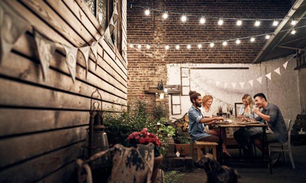 Friends eating dinner under garden solar lights.