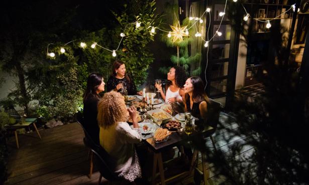 A goup of friends eating dinner under garden solar lights.