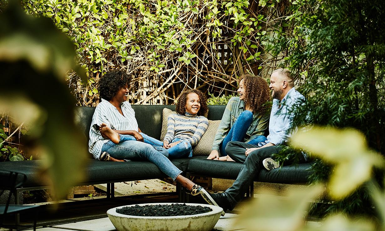 Family sitting on garden furniture