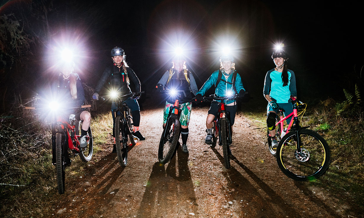 Cyclists wearing head torches and bike lights