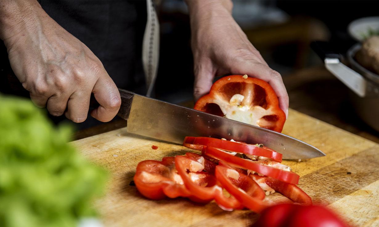 Kitchen knife chopping a pepper