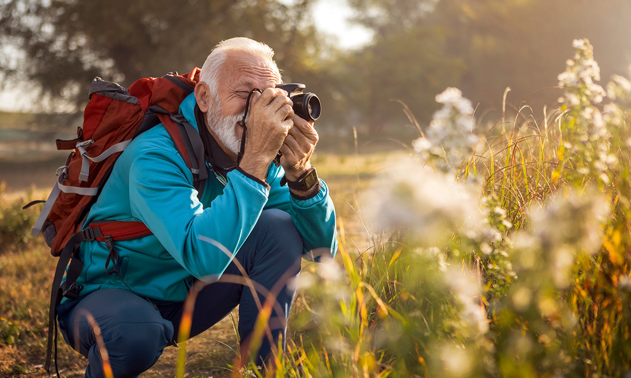 A man taking a picture of flowers outdoors