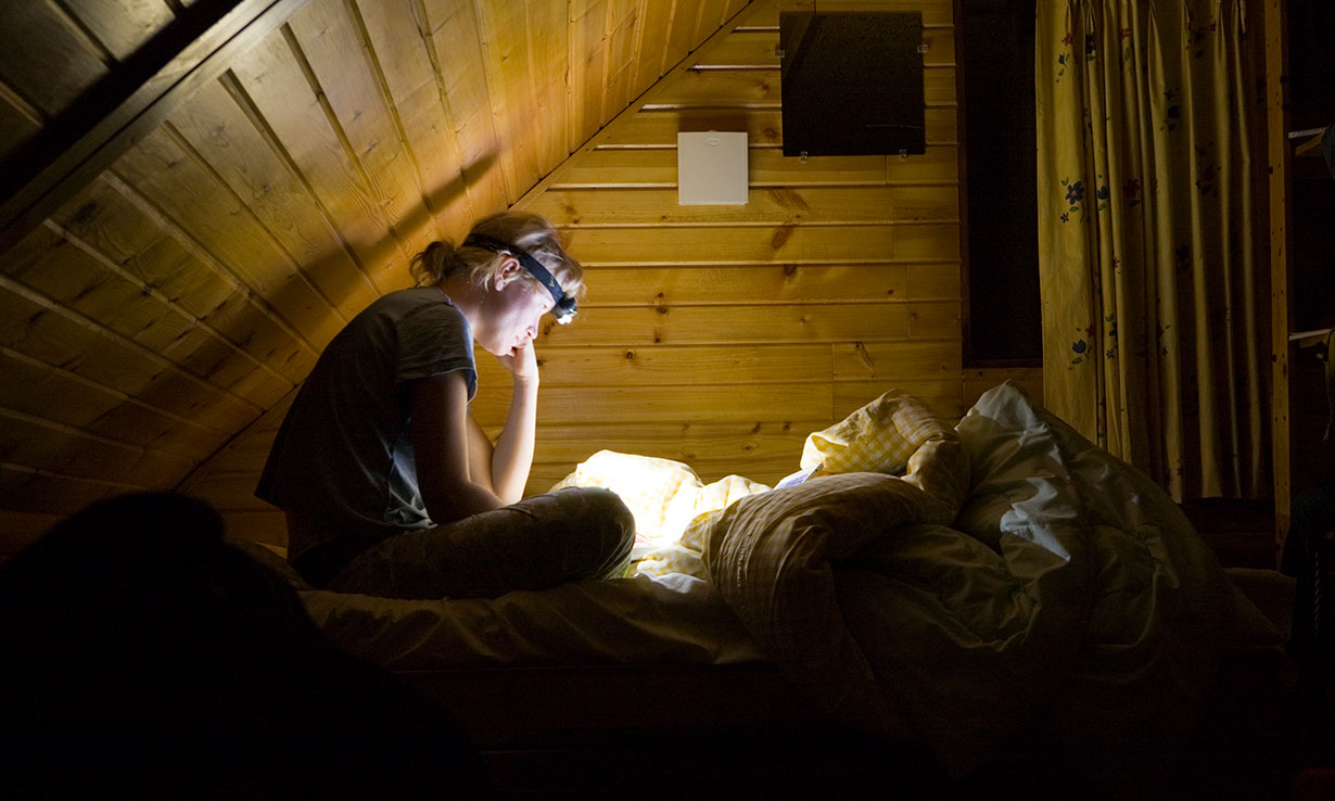 Child reading a book wearing a head torch