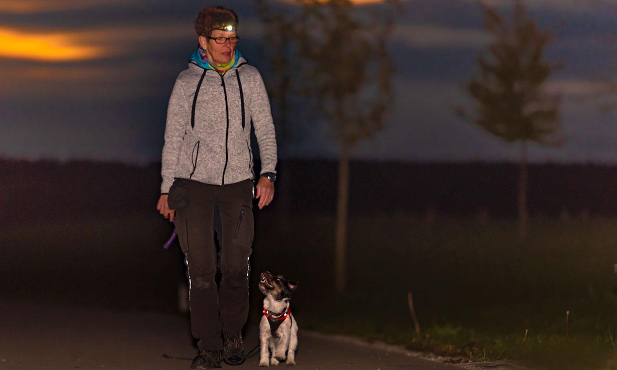 Woman walking a dog at night wearing a head torch