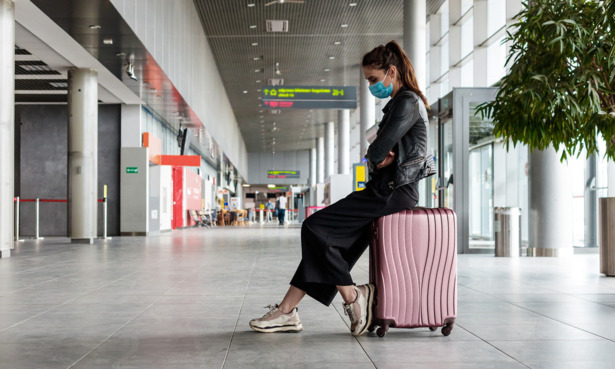 woman fed up at airport sitting on suitcase