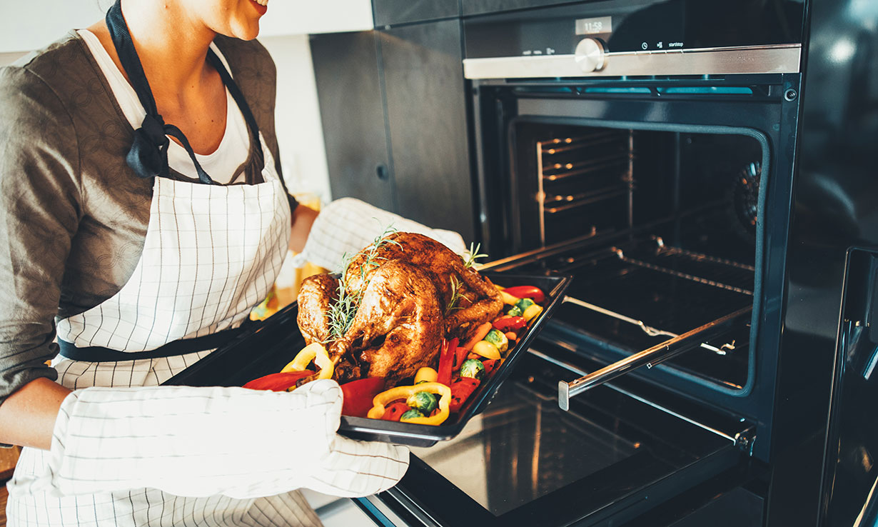 Woman preparing oven-roasted chicken