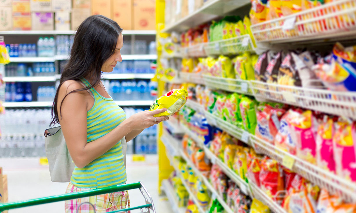 Woman looking at crisps in supermarket aisle