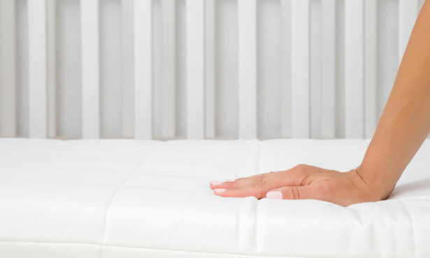 Hand pressing on cot mattress