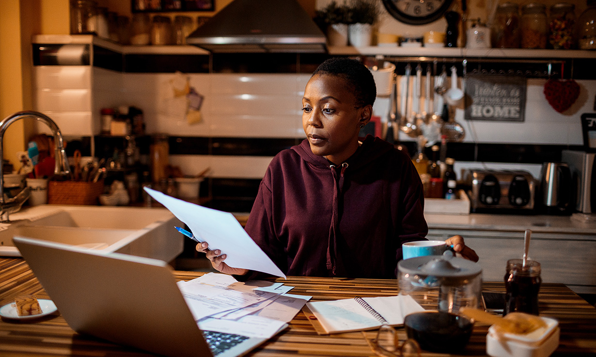 Woman sitting in a kitchen looking horrified at an energy bill