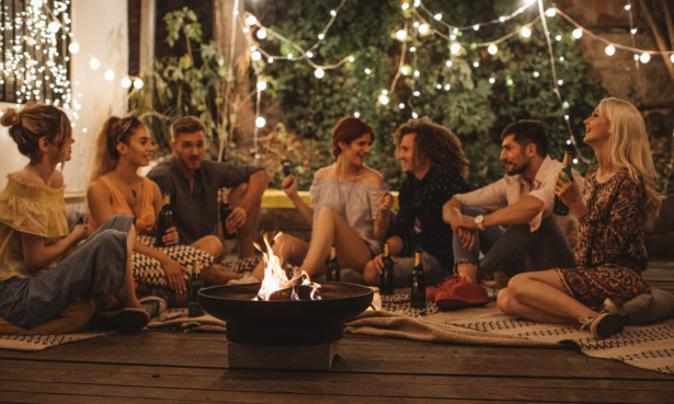 People sat at a garden party with fairy light around them