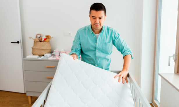 dad holding and inspecting cot mattress